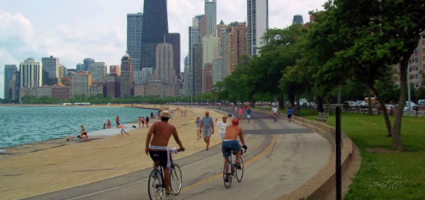 people riding their bikes on the lake front path in Chicago with skyline view